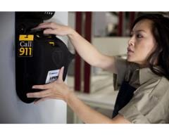 woman putting AED in wall mounted cabinet