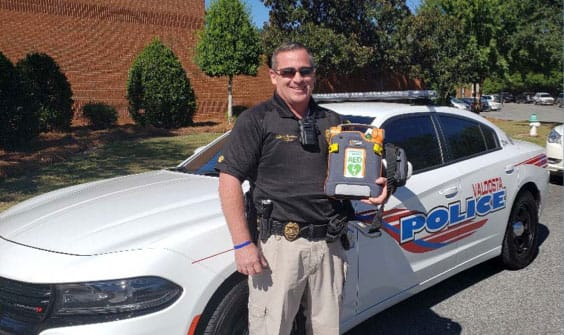 man with aed in front of patrol car