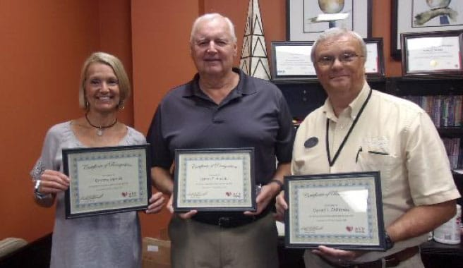 three people with certificates of recognition